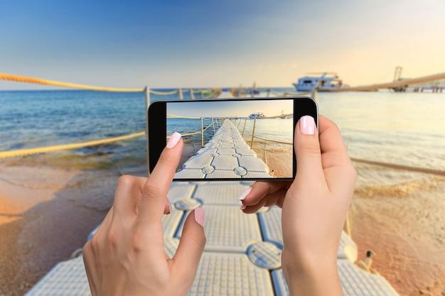 Photographie de téléphone portable d'une plage large vue horizontale. gros plan, main, tenue, téléphone, tir, plage
