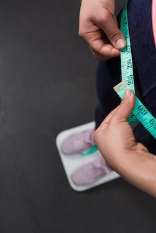 Photographie verticale des mains de femme en gros plan portant des vêtements de sport mesurant la taille avec un ruban à mesurer pouces.