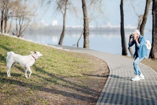 Photographier. femme mature sérieuse à prendre des photos d'un chien en marchant dans le parc