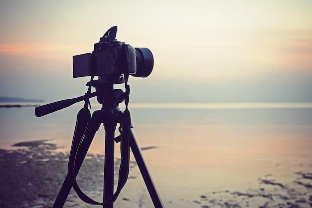 Photographier un paysage marin. la caméra miroir sur un trépied supprime l'aube de la mer. une aube rose vif.