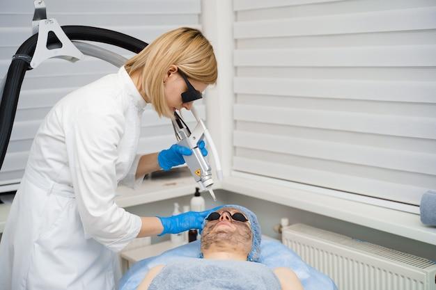 Photorajeunissement au laser et peeling au carbone du visage pour femme. masque noir. dermatologie et cosmétologie. utilisation d'un laser chirurgical.