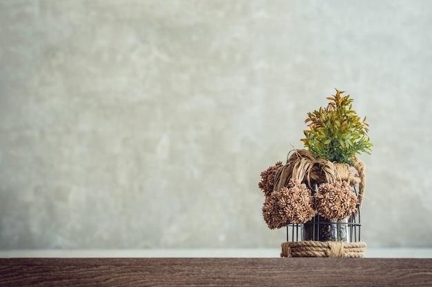 Photos de l'avant d'un pot de plantes ornementales posé sur une table en bois avec un fond de mur de ciment