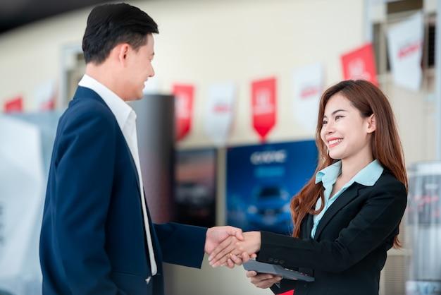 Des photos de clients et de vendeurs asiatiques, main dans la main, heureux d'acheter de nouvelles voitures qui concluent des accords de vente avec des concessionnaires automobiles chez des concessionnaires automobiles.