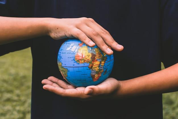 Photos de concept de jour de la terre avec la main tenant le globe terrestre