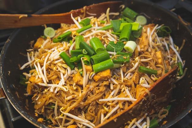 Les photos de la cuisine cuisinant des plats thaïlandais. le pad thai est la nourriture nationale de la thaïlande, vendue dans les restaurants thaïlandais du monde entier.