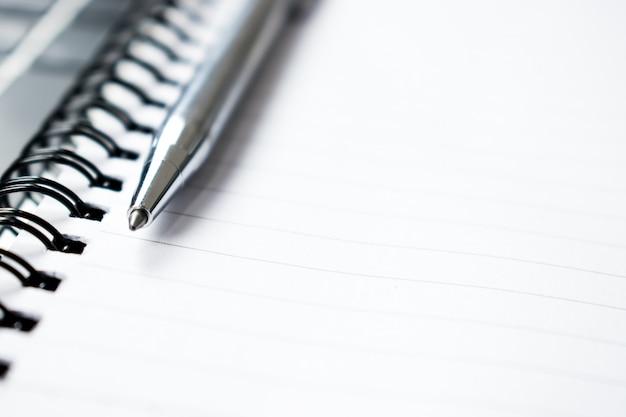 Photos du stylo placé sur le cahier. fermer.
