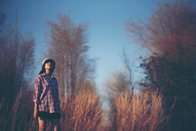 Photos de fille asiatique avec herbe naturelle et ciel, détendez-vous au coucher du soleil