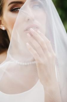 Photos de la mariée magnifique posant sous le voile à l'extérieur