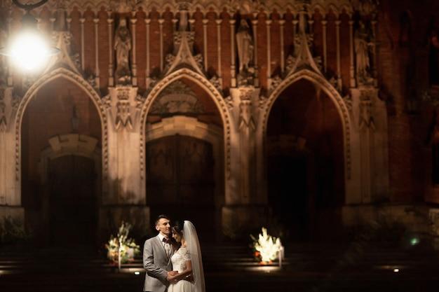 Photosession de nuit du couple de mariage à cracovie. les nouveaux mariés marchent autour de l'église