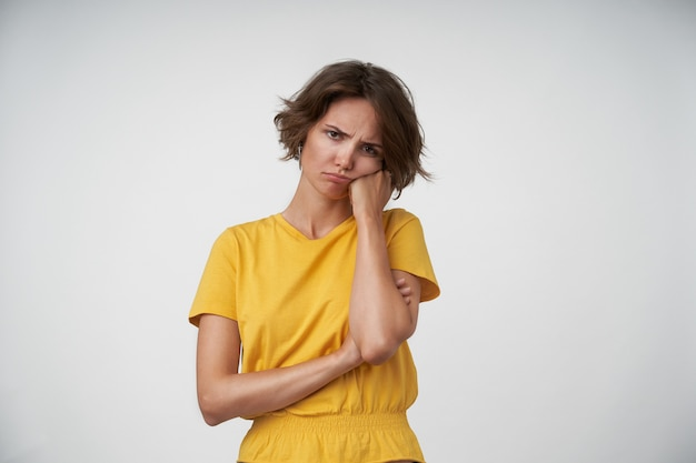 Photot d'intérieur de jeune femme brune s'ennuie avec une coupe courte, penchant la tête sur la main levée, à la recherche d'un visage ennuyeux et fronçant les sourcils, isolé