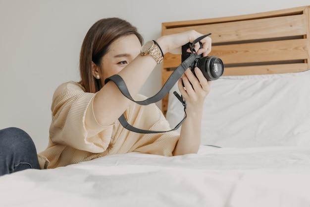 Phototographe femme vérifiant le viseur de l'appareil photo dans son propre appartement