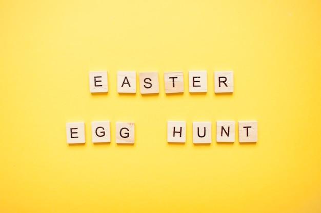 Phrase chasse aux œufs de pâques faite de blocs de bois sur un jaune clair