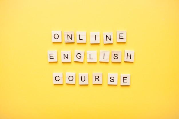 Phrase cours d'anglais en ligne fabriqué à partir de blocs de bois sur un jaune clair
