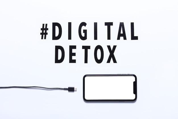 Phrase de désintoxication numérique et smartphone avec câble de charge débrochable. fond blanc, hashtag, vue de dessus.
