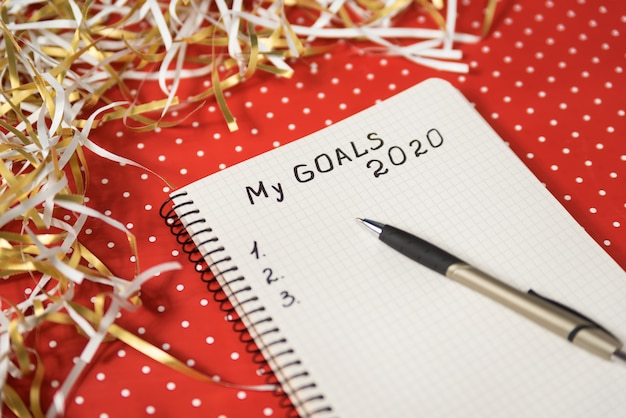 Phrase my goals dans un cahier, un stylo noir.