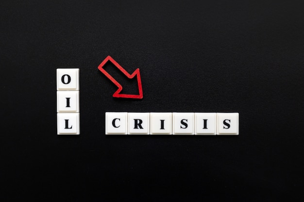Phrase oil crisis faite de lettres majuscules en plastique avec une flèche rouge qui tombe
