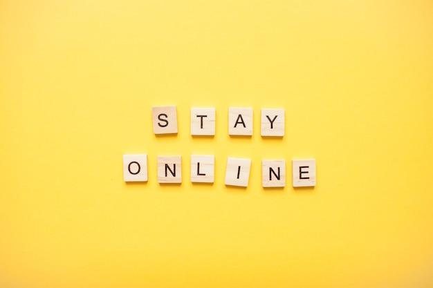 Phrase rester en ligne à partir de blocs de bois sur un fond jaune clair
