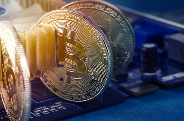 Physical gold bitcoin coin sur une carte vidéo d'ordinateur. nouvelle crypto-monnaie mondiale indépendante.
