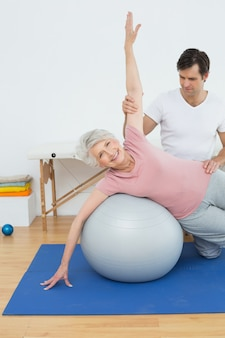 Physiothérapeute aidant une femme senior avec ballon d'yoga