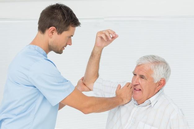 Physiothérapeute aidant un homme senior à étirer sa main