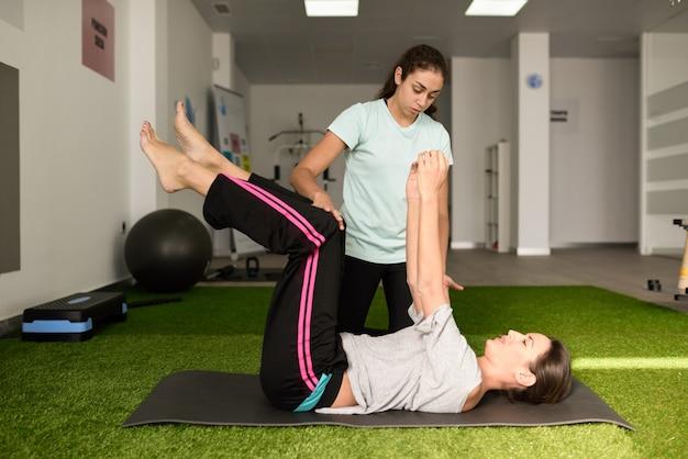 Physiothérapeute aidant la jeune femme caucasienne avec l'exercice