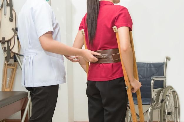 Physiothérapeute aidant le transfert du patient en fauteuil roulant