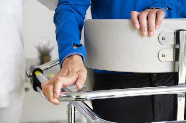 Physiothérapeute assistant un patient atteint de sclérose latérale amyotrophique.