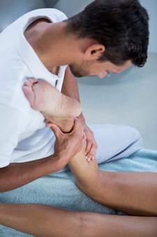 Physiothérapeute donnant un massage des jambes à une femme