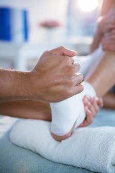 Physiothérapeute donnant un massage des pieds à une femme