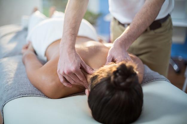 Physiothérapeute donnant une thérapie physique au cou d'une patiente