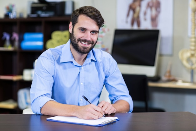 Physiothérapeute écrit sur un presse-papiers