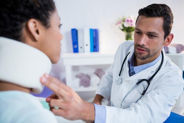 Physiothérapeute examinant le cou d'une patiente