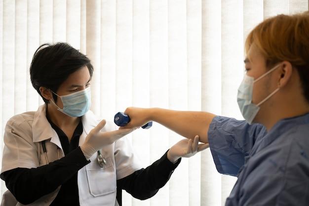 Physiothérapeute examinant le traitement du bras blessé du patient.