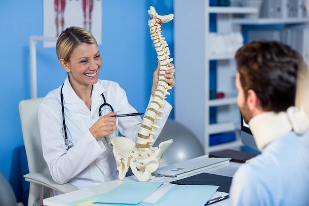 Physiothérapeute expliquant le modèle de la colonne vertébrale au patient