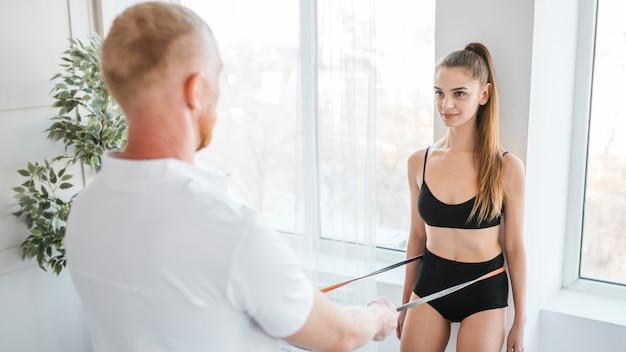 Physiothérapeute faisant des exercices de cordon élastique avec femme
