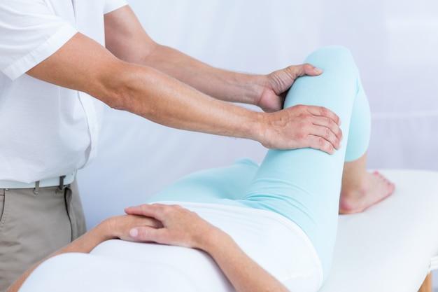 Physiothérapeute faisant massage des jambes à son patient