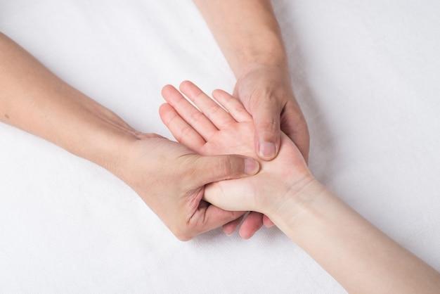 Physiothérapeute faisant un massage des mains en cabinet médical