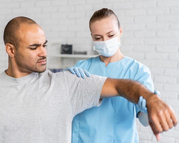 Physiothérapeute femelle contrôle le coude de l'homme