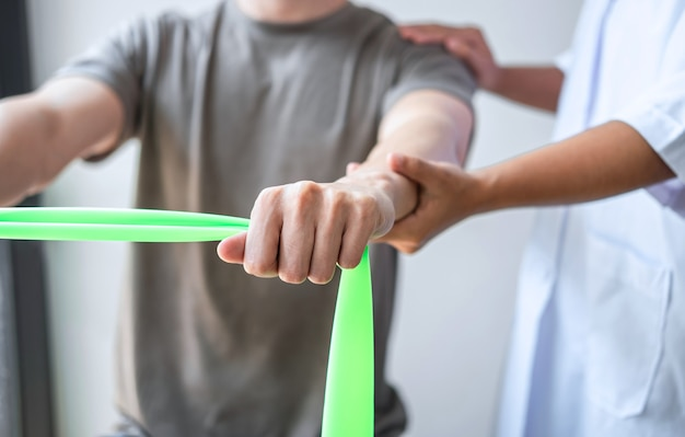 Physiothérapeute féminine travaillant sur le traitement du bras blessé d'un patient masculin athlète, étirement et exercice