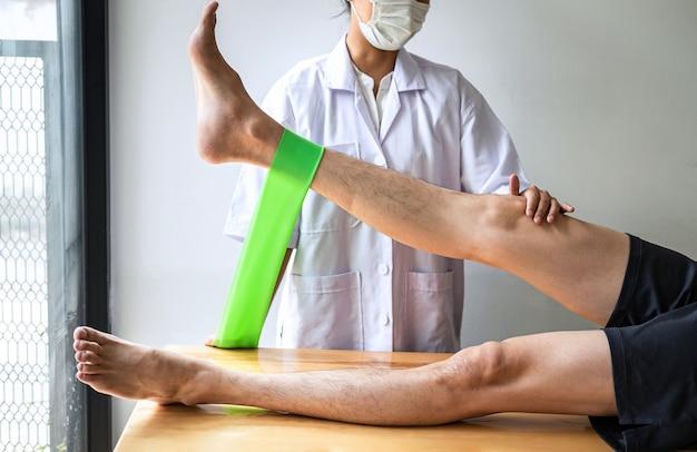 Physiothérapeute féminine travaillant sur le traitement de la jambe blessée d'un patient masculin, faisant des exercices de la douleur de thérapie de réadaptation en clinique.