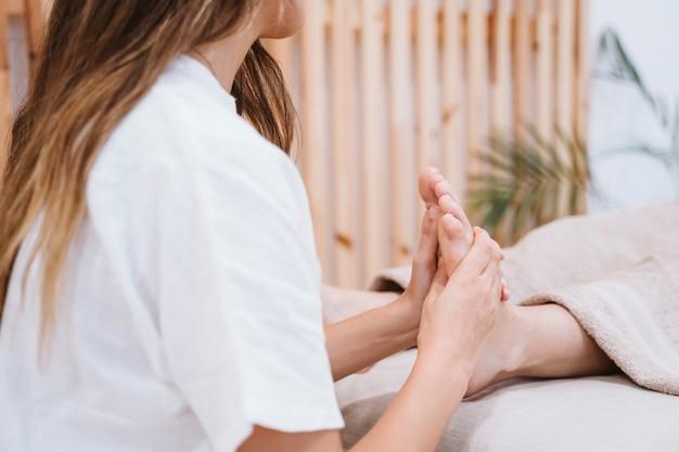 Physiothérapeute femme donnant un massage des pieds à une patiente en clinique
