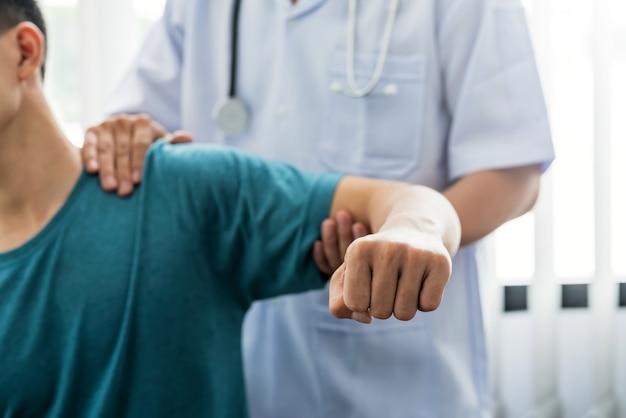 Physiothérapeute homme étirant l'épaule et le patient du bras dans une clinique.