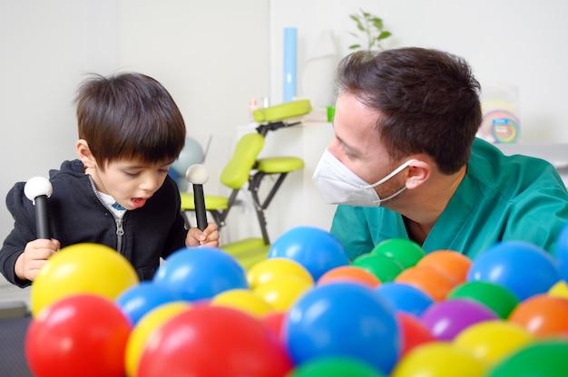 Physiothérapeute jouant avec des enfants, atteints de paralysie cérébrale.