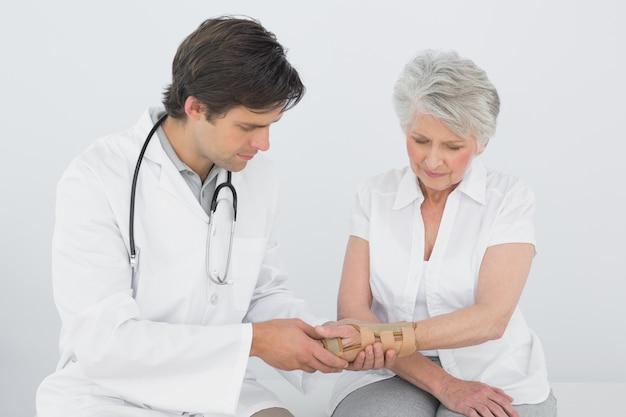Physiothérapeute mâle examinant un poignet womans senior
