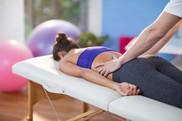 Physiothérapeute masculin donnant un massage du dos à une patiente