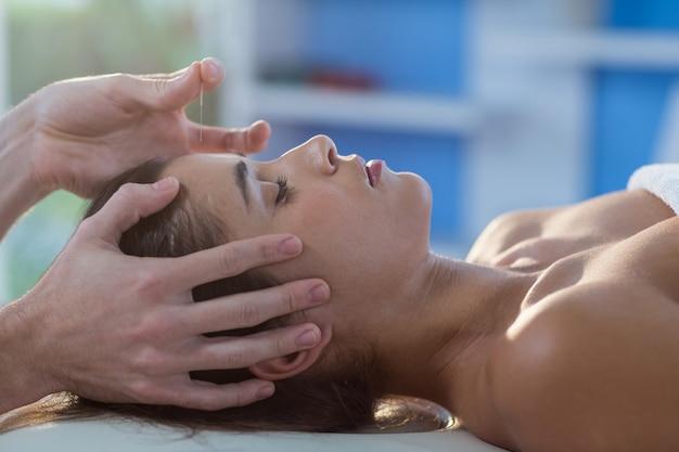Physiothérapeute masculin donnant un massage de la tête à une patiente