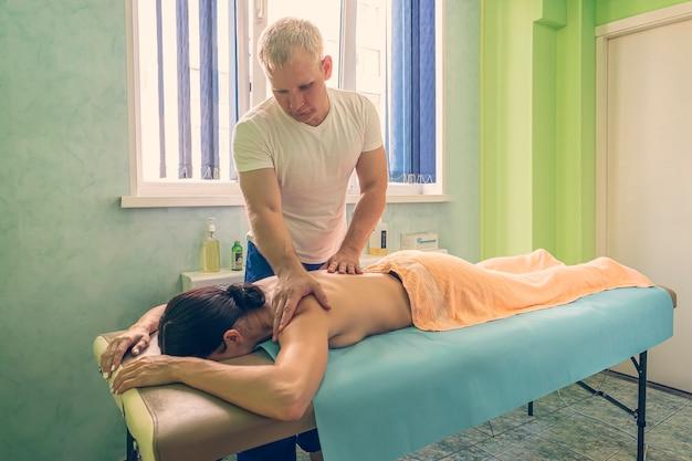 Un physiothérapeute masculin donne un massage du dos à une jeune fille sur la table de massage dans la salle de physiothérapie de l'hôpital. ostéopathe