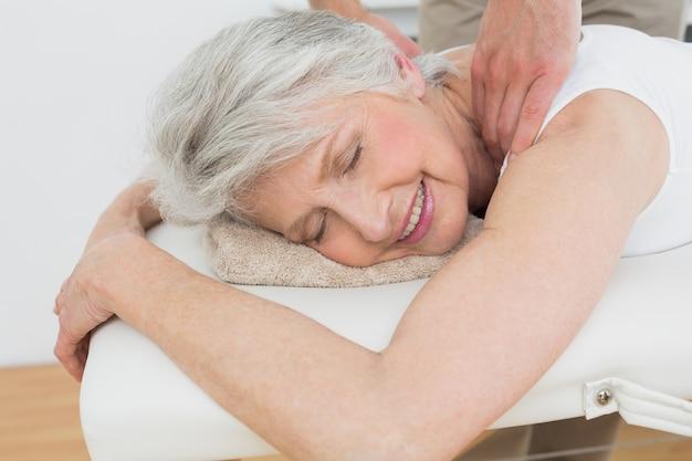 Physiothérapeute massant une épaule womans senior