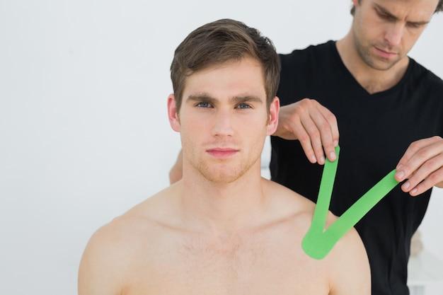Physiothérapeute mettant sur le ruban kinésio sur l'épaule des patients