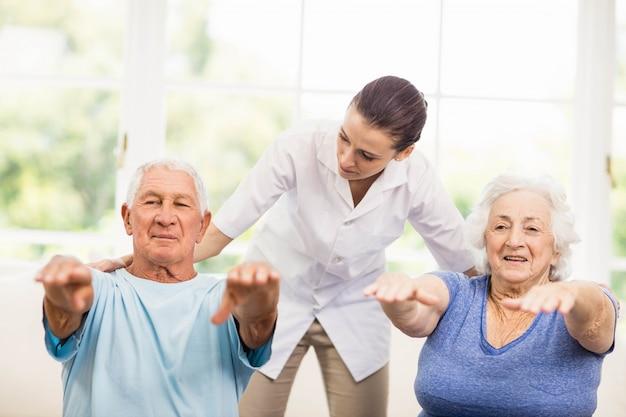 Physiothérapeute prenant en charge des patients âgés malades à la maison